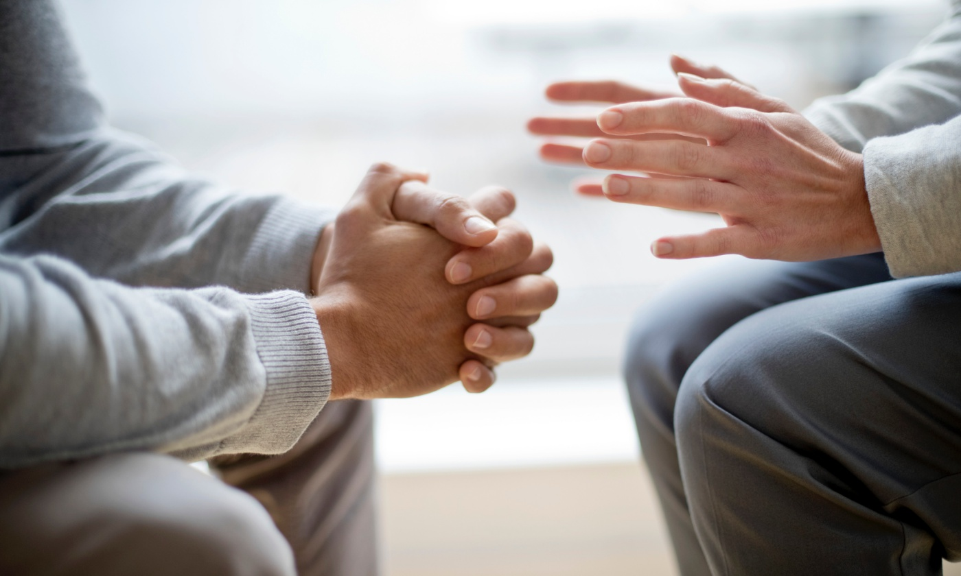 Two people having a difficult conversation, one with hands bunched together receiving feedback and the other with palms open giving feedback