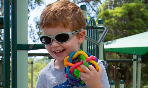 Hugo smiles at the playground and is holding a colourful tactile toy